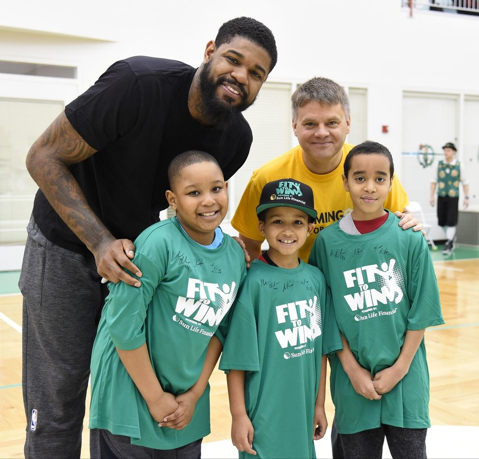 Celtics power forward Amir Johnson (L) with Ed Milano, VP, Sun Life Financial, and YMCA youth participants of Sun Life Fit to Win program.
