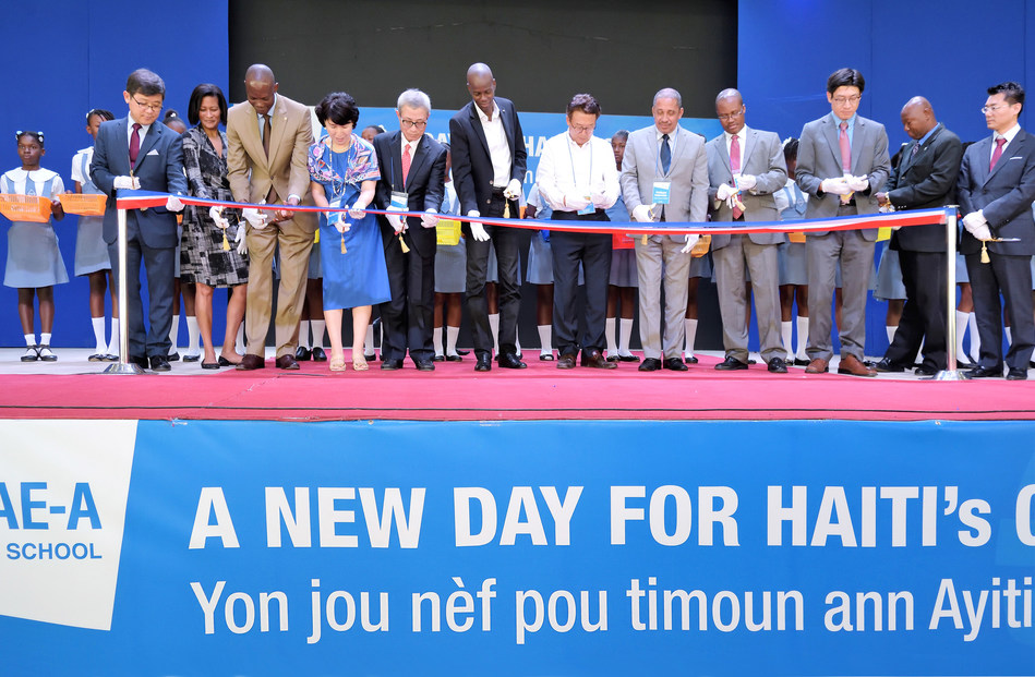 Woong-Ki Kim, Chairman of Sae-A, Jovenel Moise, the President of Haiti, Louis-Mary Cador, Director General of the Ministry of Education in Haiti, and Yeong-Sun Jung, the Head of Office for the Korea International Corporation Agency, are cutting the ribbon with parents and students at the ribbon-cutting ceremony of S&H Secondary School on March 24.