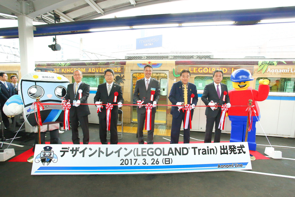 """Nicknamed """"the LEGOLAND Train,"""" a commuter train themed after attractions at LEGOLAND Japan began service on the Nagoya Rinkai Rapid Transit's Aonami Line on March 27. Together with the start of service, a departure ceremony for the Design Train was held on Sunday, March 26 with local officials, Buddy, LEGOLAND Japan's mascot, and Aotetsu-kun, mascot for the Aonami Line."""