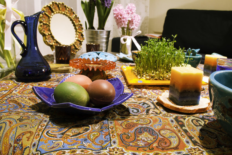 """Traditional haftseen table which includes seven symbols that represent life, all starting with the letter """"s."""" To name a few, sabzeh (wheat sprouts) represents rebirth, sib (apple) represents beauty or health, and serkeh (vinegar) represents patience. For Iranians, Nowruz symbolizes change. It heralds the end of the dark, dull days of winter, and the arrival of the flourishing days of spring."""