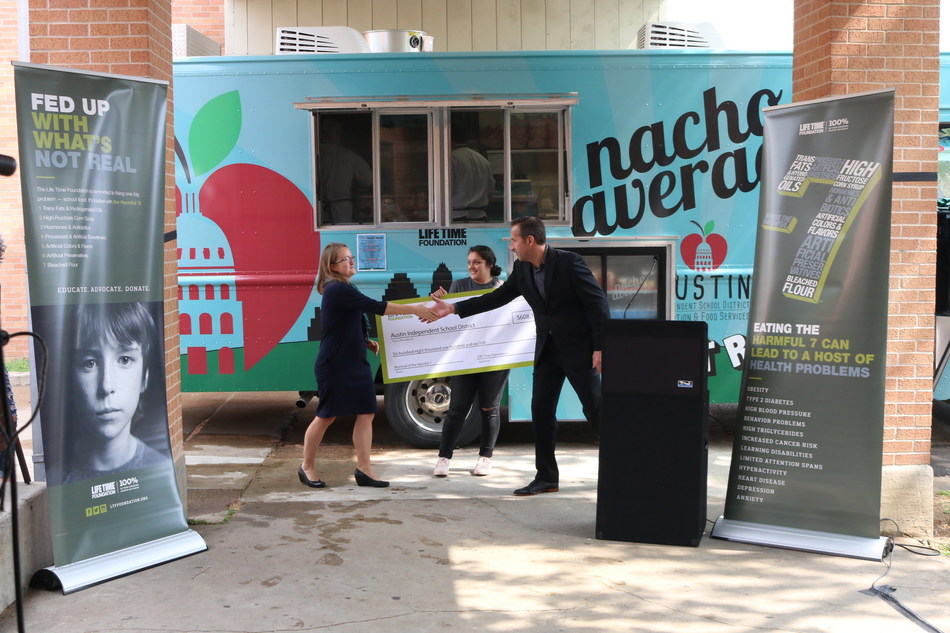 """Life Time Foundation President Jason Thunstrom presents a grant of $608,100 from the Foundation to Anneliese Tanner, Director, Austin Independent School District Nutrition and Food Services during a presentation event introducing the district's first mobile food vehicle named, """"Nacho Average Food Truck"""" on Friday, March 24 at William B. Travis High School in Austin, Texas."""