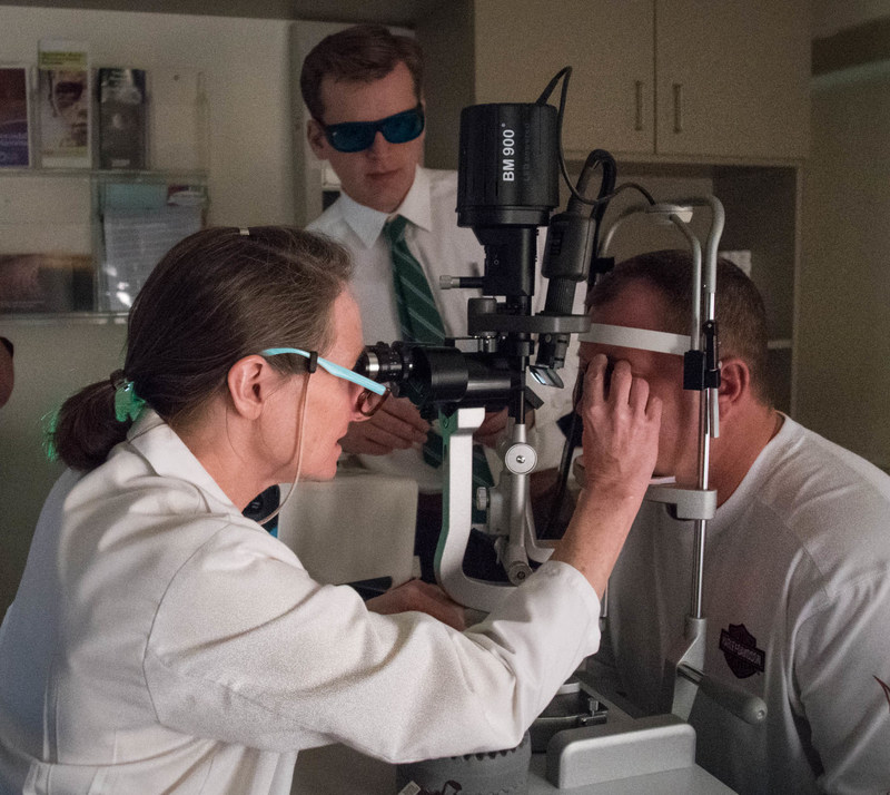 Wills Eye Hospital's Carol Shields, MD examines patient (clinical study participant). Oncology research fellow, wearing protective eyewear, also observes. Photo courtesy: Roger Barone / Wills Eye Hospital.