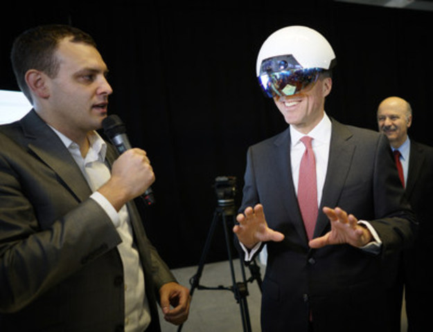 Ben Holfeld of Accenture's AI practice, left, helps Canadian Finance Minister Bill Morneau, right, use a DAQRI Smart Helmet during the launch of the Vector Institute for AI at the MaRs Discovery District in Toronto, Ont. on Thursday, March 30, 2017.  THE CANADIAN PRESS IMAGES/J.P. Moczulski (CNW Group/Accenture)