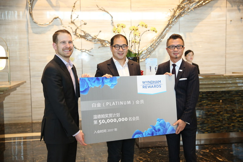 Noah Brodsky, Wyndham Hotel Group senior vice president of worldwide loyalty and engagement, left, and Leo Liu, Wyndham Hotel Group president and managing director for Greater China, right, congratulate Samuel Xu on becoming Wyndham Rewards' 50 millionth member. Mr. Xu enrolled in the award-winning program while staying at the newly opened Wyndham Grand Xiamen.