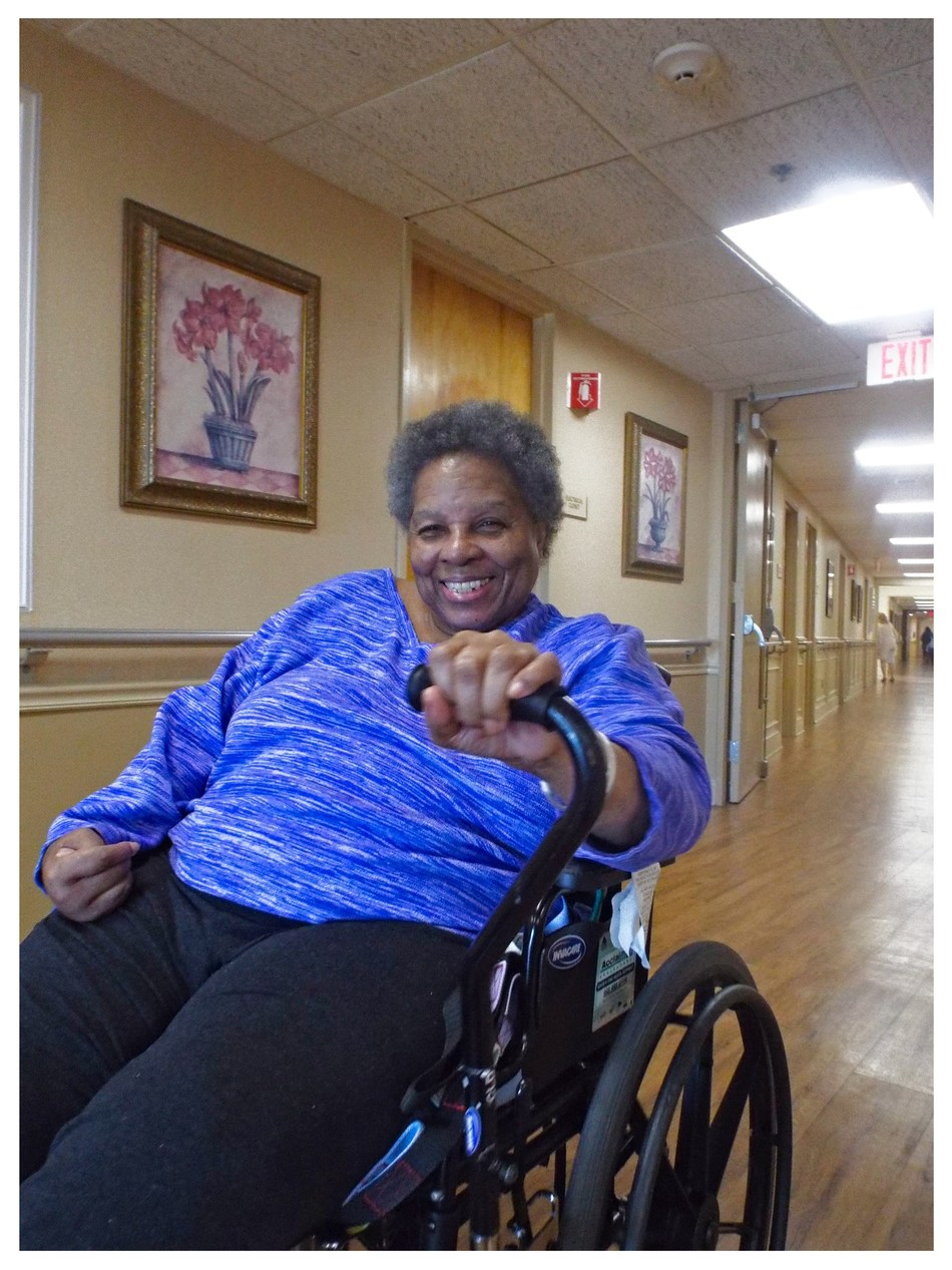 Margaret is all smiles as she self propels with her one arm drive wheelchair.