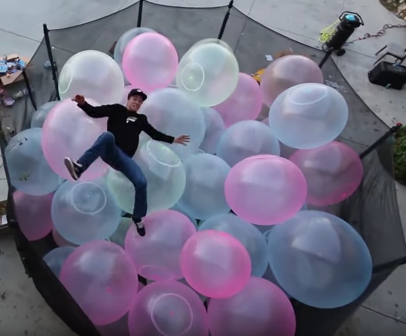 """YouTube's """"Funk Bros."""" filled a trampoline with Super Wubbles, then jumped onto it from the second story of their house."""