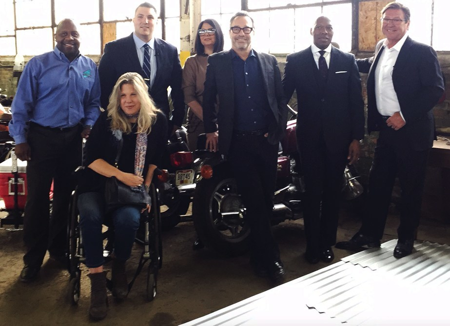 """The team of investors from """"Cleveland Chain Reaction"""" poses for a picture with show host, Kenny Crumpton, in the Skidmark Garage located in the Ingenuity shared maker space (from left to right) Kenny Crumpton, host; Claudia Young, owner of the Velvet Tango Room and Citizen Pie; Justin Miller, CEO and founder of CleanLife Energy; Lillian Kuri, vice president of the Cleveland Foundation; Alan Glazen, founder of GlazenUrban; Andrew Jackson, CEO of Elson's International; and Fred Geis, CEO of Heming"""
