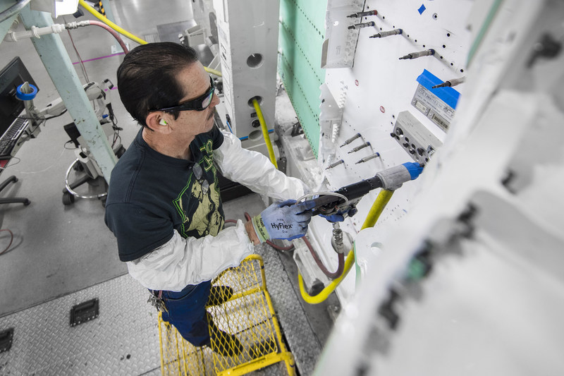 Lockheed Martin aircraft assembler Daniel Molina uses a power feed drill motor using forced mechanical oscillation to reduce chip size. The improved chip formation reduces drill times, improves hole quality and increases tool life for deep stack applications.