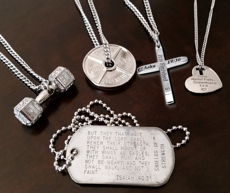 After two decades in business, Shields of Strength's product line features more than 400 items. The dog tag, in foreground, marked the first Shields of Strength design in 1997.  Today, the product line includes the popular dumbbell and weight plate pendant necklaces for athletes; for Easter, the Cross Necklace engraved with John 19:30, and the Love Never Fails Heart Necklace with cutout cross; apparel, thermal mugs and even fishing poles. Every item is adorned with scripture.