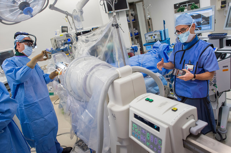 Dr. Alon Mogilner (L) and Dr. Michael H. Pourfar (R) perform a deep brain stimulation procedure at NYU Langone Medical Center in New York.