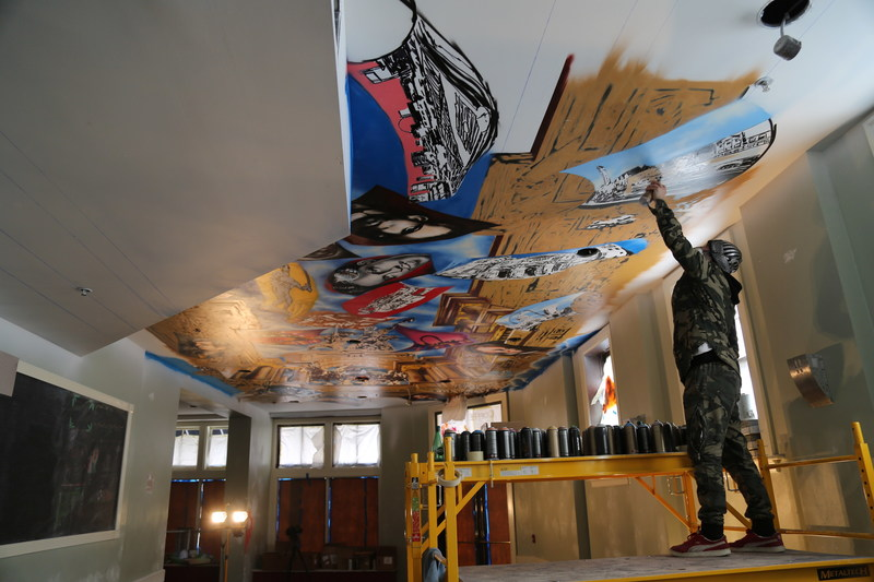 Artist, Paco Rosic works on his latest project, the History of St. Louis mural, on the ceiling of Cafe Piazza.