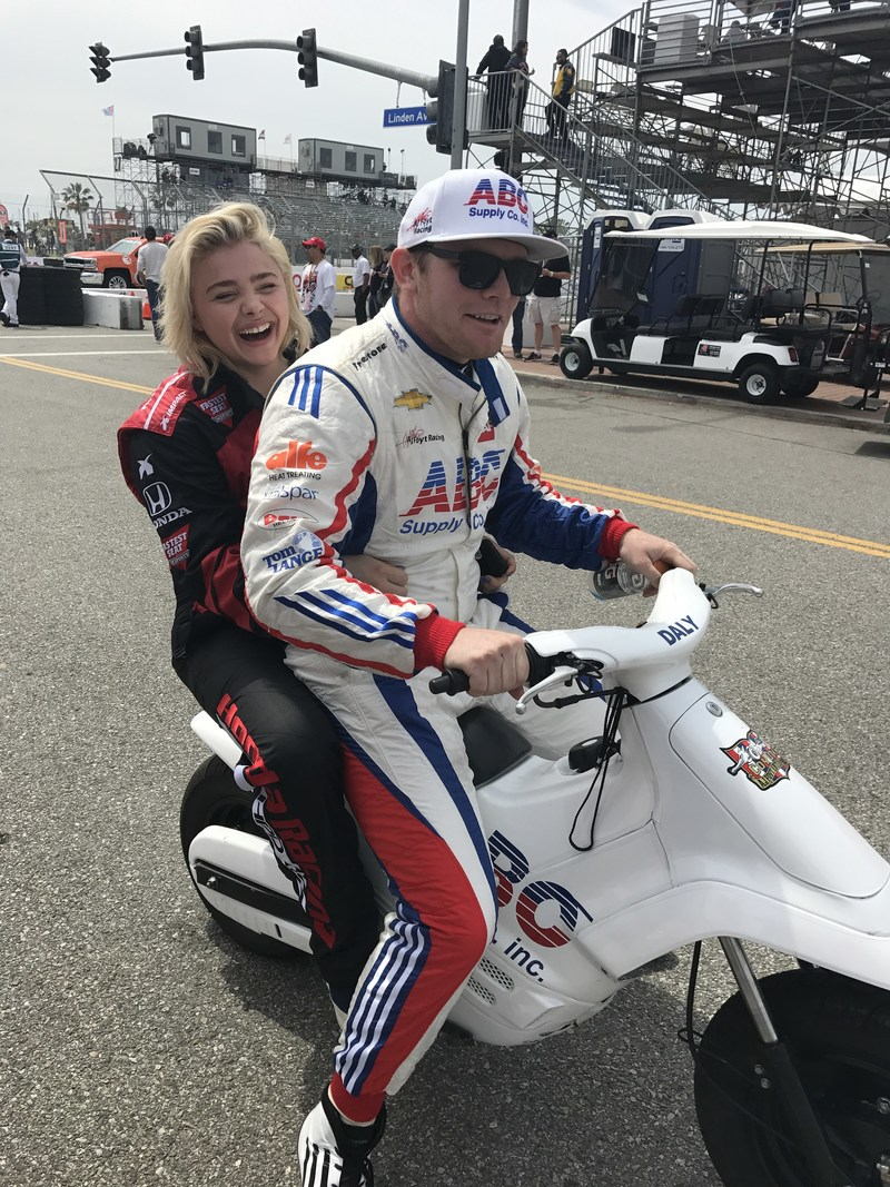 Verizon IndyCar Series driver Conor Daly gives actress Chloe Grace Moretz a lift to the INDYCAR pits before the start of the Toyota Grand Prix of Long Beach. Moretz was one of several celebrities who attended Sunday's race won by Schmidt Peterson Motorsports driver James Hinchcliffe. (INDYCAR Photo)
