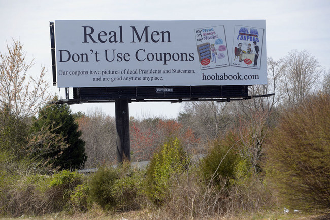 """Billboard promoting launch of two new books replacing """"Real Men Provide, Real Women Appreciate It,"""" located on Rt 40 in Greensboro, North Carolina."""