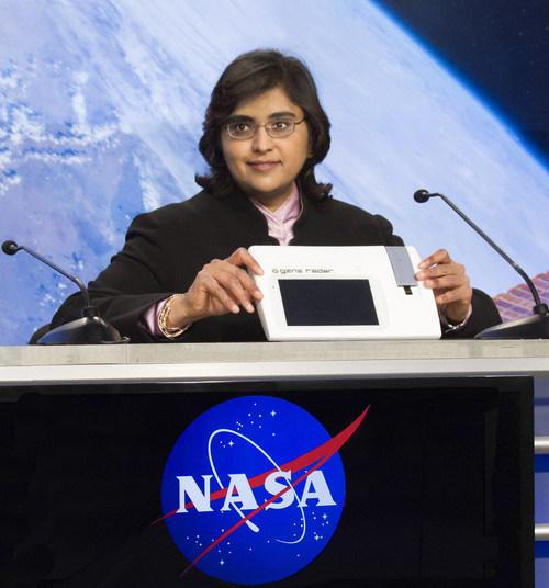 Dr. Anita Goel, M.D., Ph.D., demonstrates the highly portable Gene-RADAR device to NASA scientists.