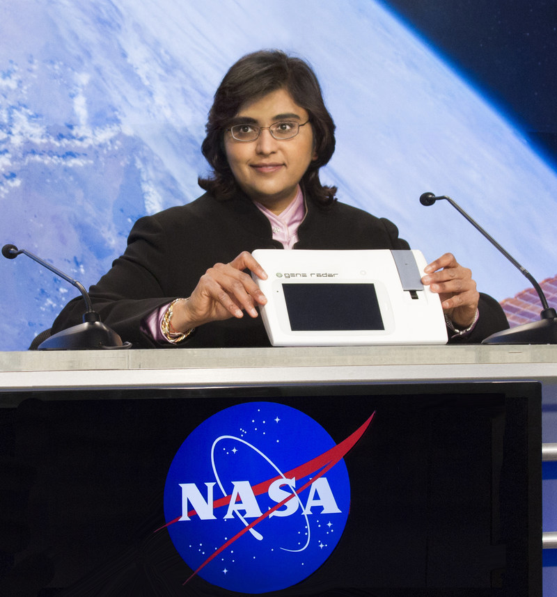 Dr. Anita Goel, M.D., Ph.D., demonstrates the highly portable Gene-RADAR device to NASA scientists.