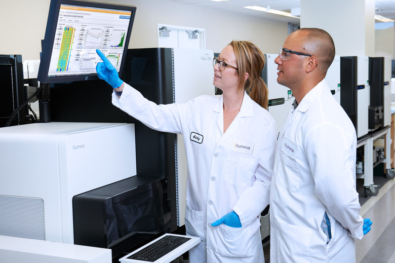 Illumina researchers reviewing data on a HiSeq Sequencing Instrument