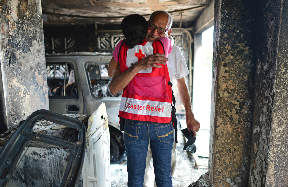 A Red Cross worker consoles Mr. Luis Monzon after he suffered a fire in his home that same morning. The fire was caused by his car and spread to the majority of his house.