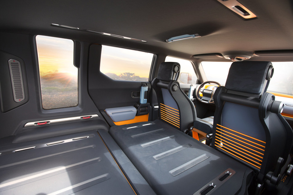 Rear passenger seats fold completely flat to expand storage capacity. Blue-colored storage boxes carry small items, while orange-painted areas serve as open holds.