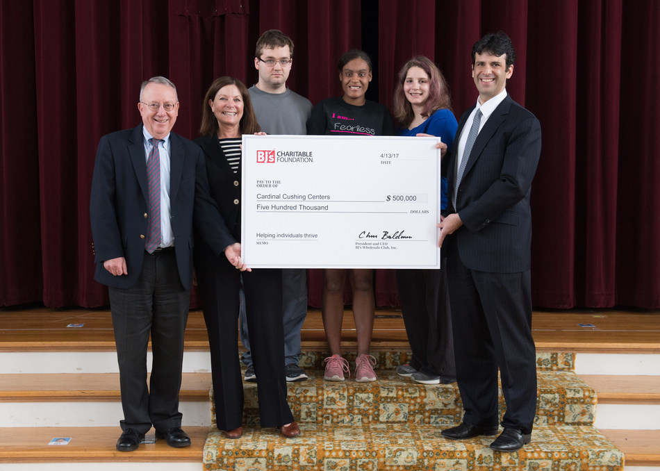 Lee Delaney, executive vice president and chief growth officer at BJ's Wholesale Club (right), presents a two-year, $500,000 grant to Peter O'Meara, president and CEO of Cardinal Cushing Centers (left), and Jansi Chandler, vice president of development (second from left) in Hanover, Mass. on Thursday, April 13, 2017. Also pictured, starting from second from left, are Cardinal Cushing students Alex Endlich, Jai'lyn Jackson and Jordyn Cook. (Gretchen Ertl/AP Images for BJ's Wholesale Club)