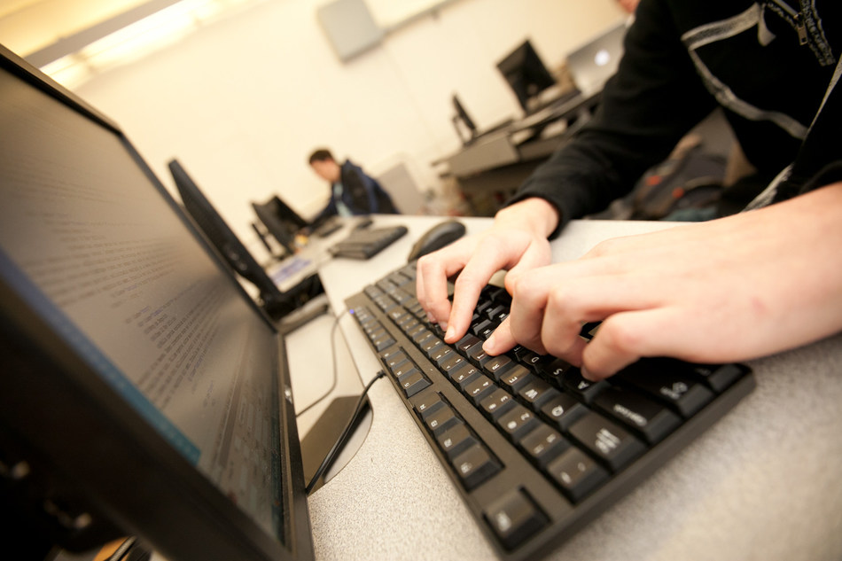 A student works on an online project for one of Webster University's online courses.