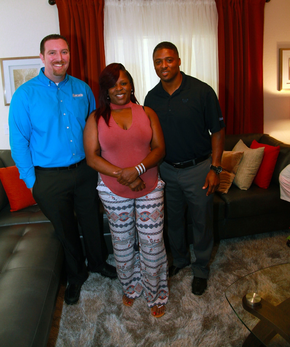 (L to R): Aaron's Regional Manager Daniel Stevens, new homeowner Keyona Thompson and former NFL star Warrick Dunn tour Thompson's new home filled with furniture, electronics and appliances donated by Aaron's, Inc. (NYSE: AAN), a leading omnichannel provider of lease-purchase solutions, as part of Homes for the Holidays (HFTH) program sponsored by Warrick Dunn Charities and Habitat for Humanity of Pinellas County.