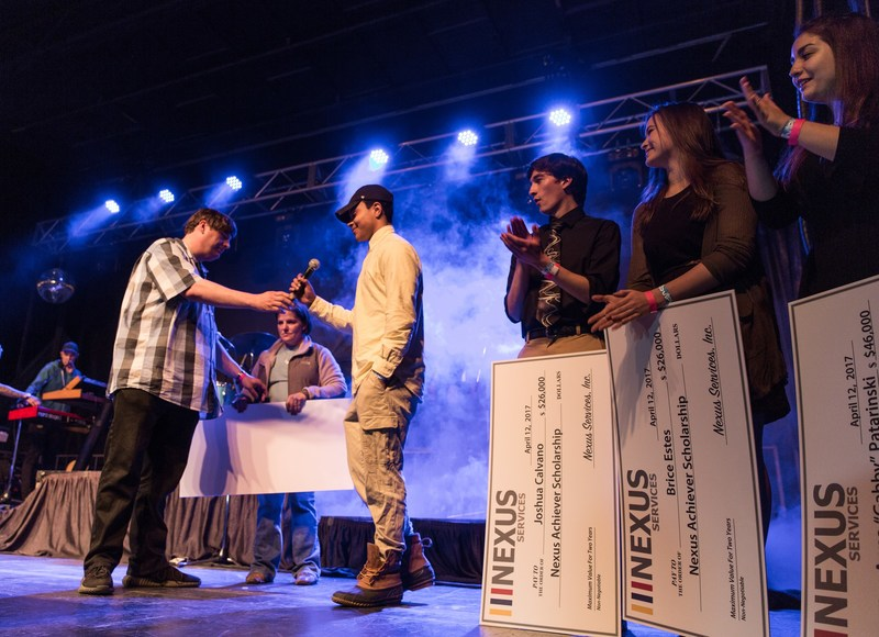 Mike Donovan, CEO and president of Nexus Services, presents Nexus scholarship winners with checks before Nate Ruess takes the stage at community concert in Verona, Virginia.