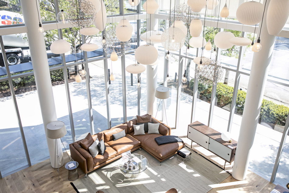 Double-height windows accentuate a living room vignette pictured from the Mezzanine above. Photo by Heidi Geldhauser.