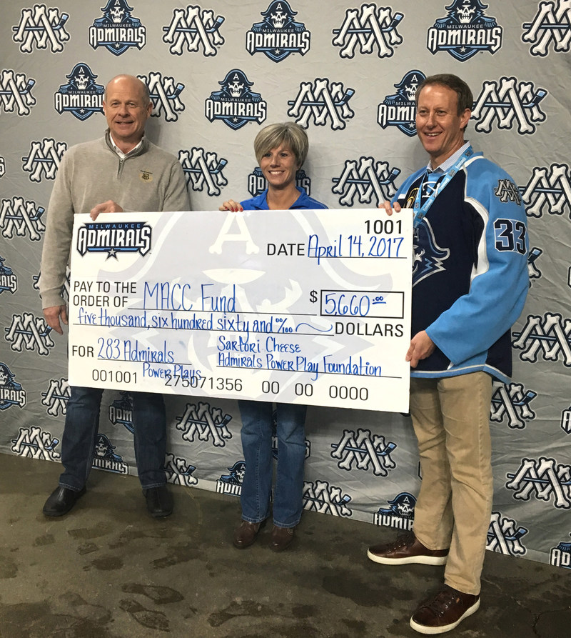 Jeff Schwager, president of Sartori Company, and Harris Turner, CEO of the Milwaukee Admirals, present a $5,660 donation to Becky Pinter, COO of the MACC Fund.