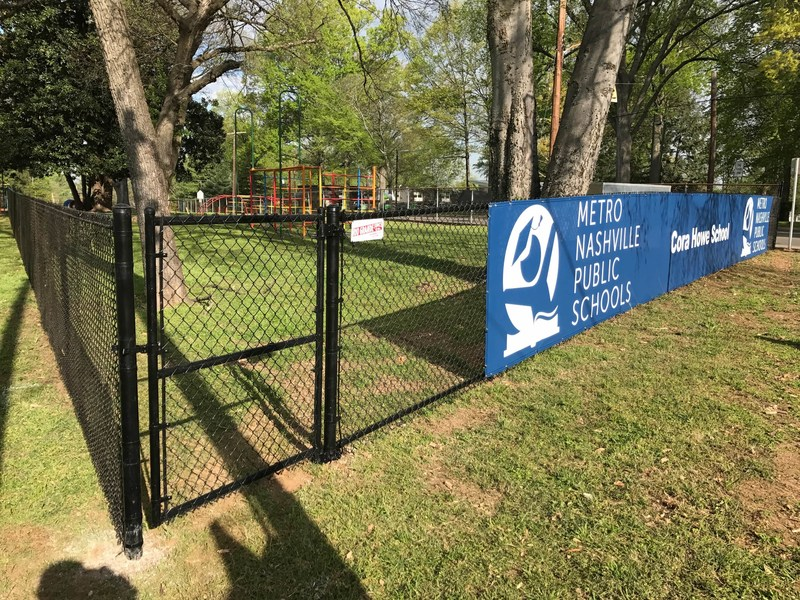 5-foot-high black chain link fence installation at Cora Howe School in Nashville, Tenn. with 50-foot wide custom logo fence screen