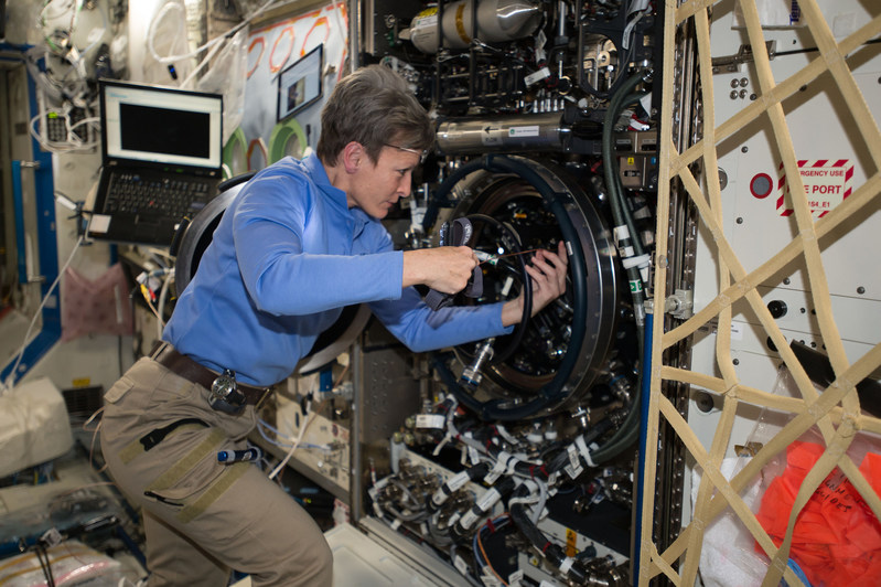 Expedition 51 Commander Peggy Whitson of NASA performs investigative troubleshooting in December 2016 on the Combustion Integrated Rack aboard the International Space Station. The rack includes an optics bench, combustion chamber, fuel and oxidizer control, and five different cameras for performing combustion experiments in microgravity. Credit: NASA