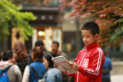 A little boy with a book for reading in The Reading Pavilion (PRNewsfoto/CCTV The Reader  Program Set .)