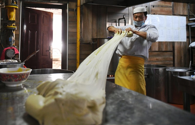 A chef mixes dough to make beef noodle at Alalan Beef-Noodles-Themed Restaurant in Chengduan District in Lanzhou, capital of northwest China's Gansu Province, April 12, 2017.