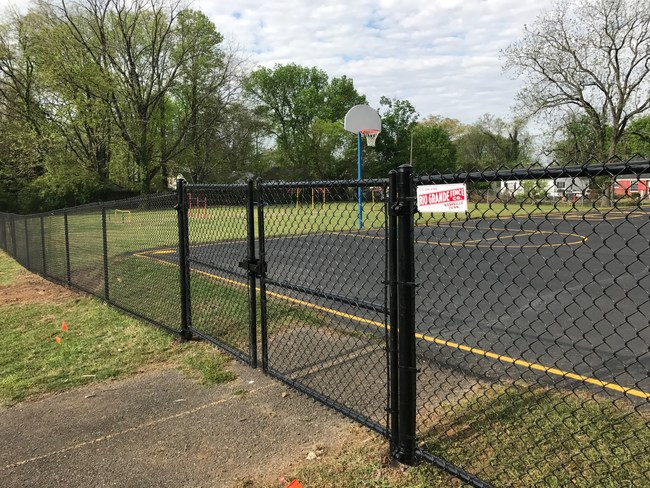 5-foot-high black chain link fence installation at Cora Howe School in Nashville, Tenn. 10-foot wide double swing gate shown with a commercial latch