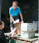 Caeli Richter, Blue Cross Blue Shield of Massachusetts, helps a staffer from the Boys and Girls Club of Boston load boxes of Healthy Snack Packs.