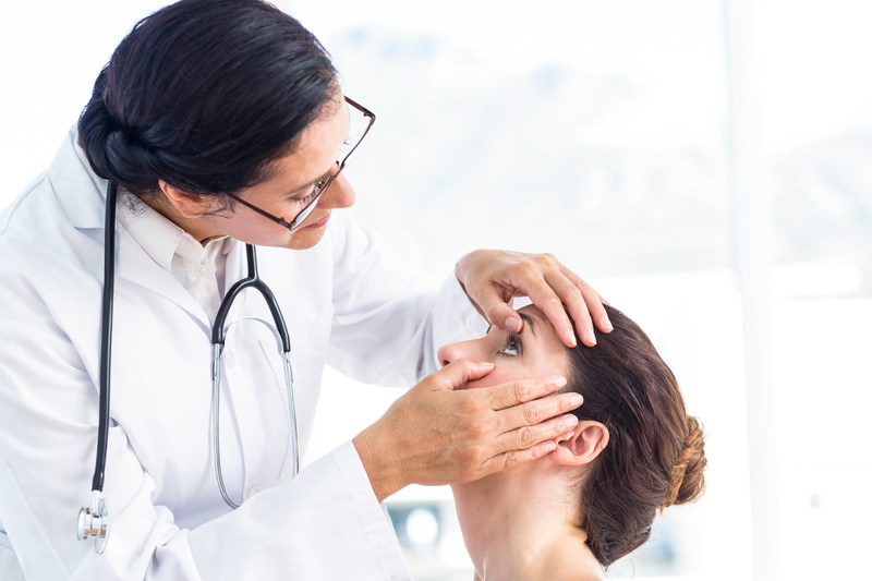 Ophthalmologist examining female patient