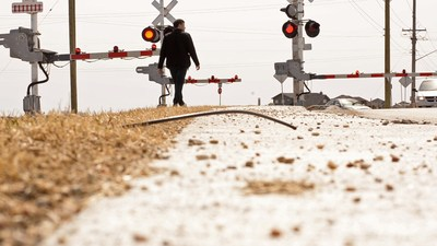 CN will join with other railways and industry groups during Canada's annual Railway Safety Week to raise awareness about the dangers of trespassing on railway property and the importance of obeying signs and devices at railway crossings. Here a pedestrian waits in front of railway gates in Winnipeg. For information on Rail Safety Week which begins Monday visit www.cn.ca/railsafety . (CNW Group/CN)