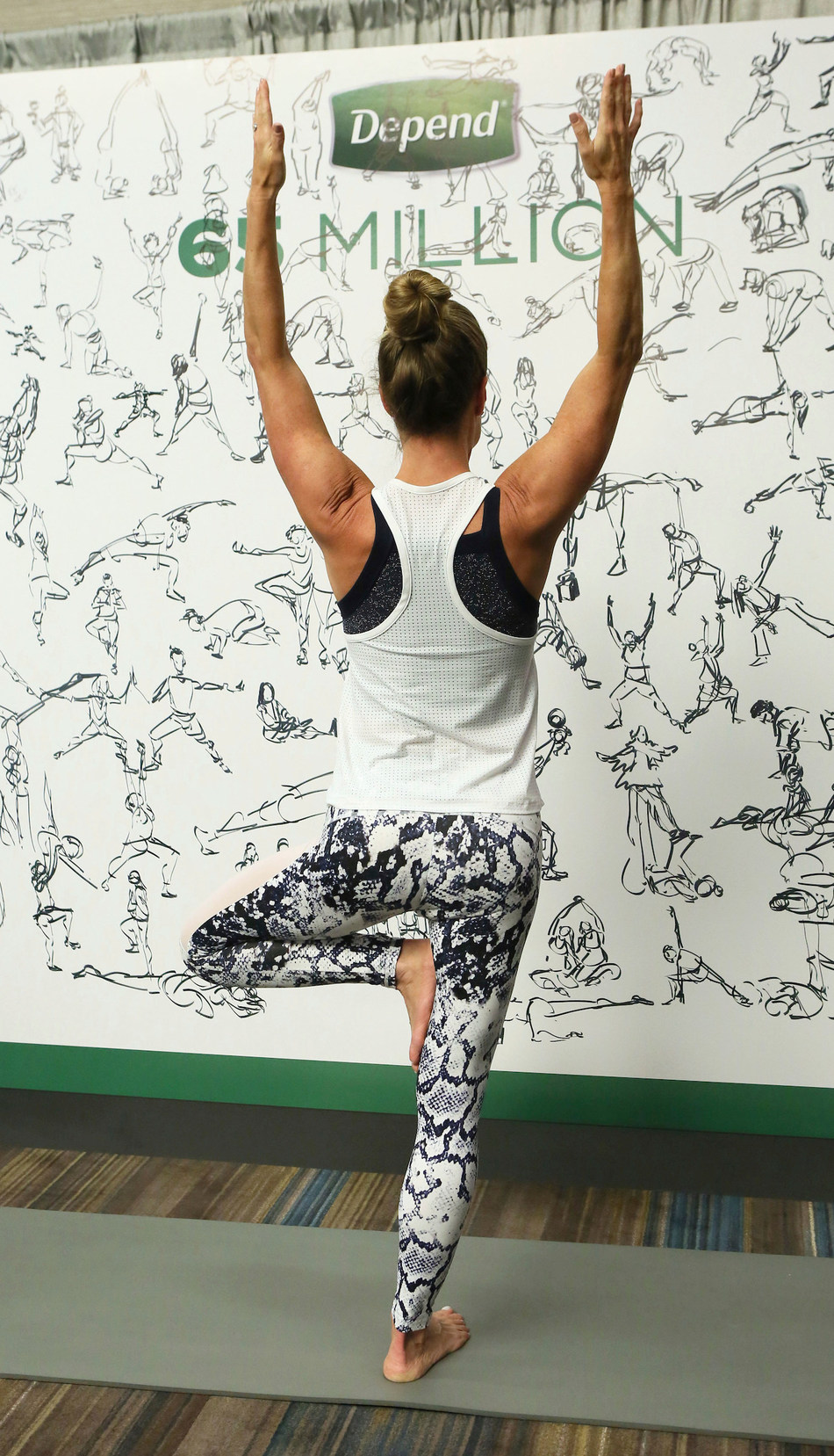 Suzie Haines poses in front of the final mural of silhouette drawings by local New York illustrator, Gil Franco, at the Depend brand exhibitor booth in New York City at the Yoga Journal Live event on Sunday, April 23, 2017. (Stuart Ramson / AP Images for Kimberly-Clark)