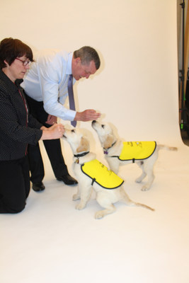 Guide dogs-in-training practice commands with their trainers Andrew and Karen. (CNW Group/CNIB)