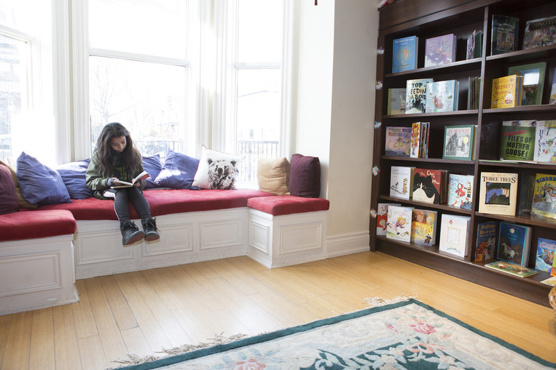 A customer reads in our beautiful storefront window. Photo Credit: David A. Fitzpatrick (CNW Group/The Children's Book Bank)