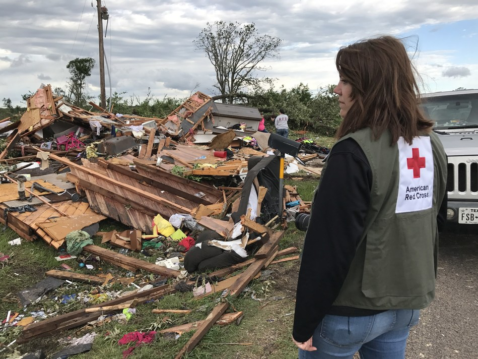 American Red Cross volunteer Bailey Moir surveys the damage in her hometown of Canton, TX after tornadoes swept through this past weekend. Moir watches as people sort through their belongings in the rubble, knowing she is headed next to help her father do the same at his home nearby.
