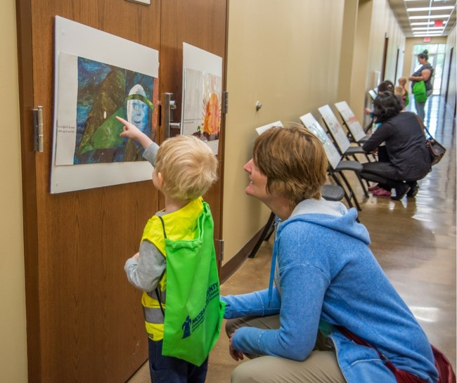 """Families explore pages of the children's book """"Construction,"""" by Sally Sutton, during the McCracken County Cooperative Extension's first StoryWalk activity day last Friday."""