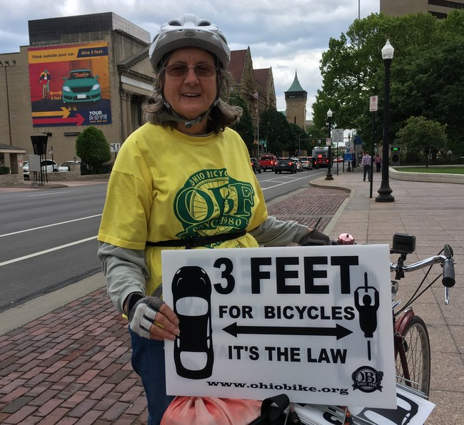 """OBF Board Member Patricia Kovacs holding three-feet signs standing close to """"Your Move Ohio"""" billboard in Columbus"""