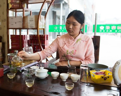 A tea specialist preparing tea for visitors during the Expo