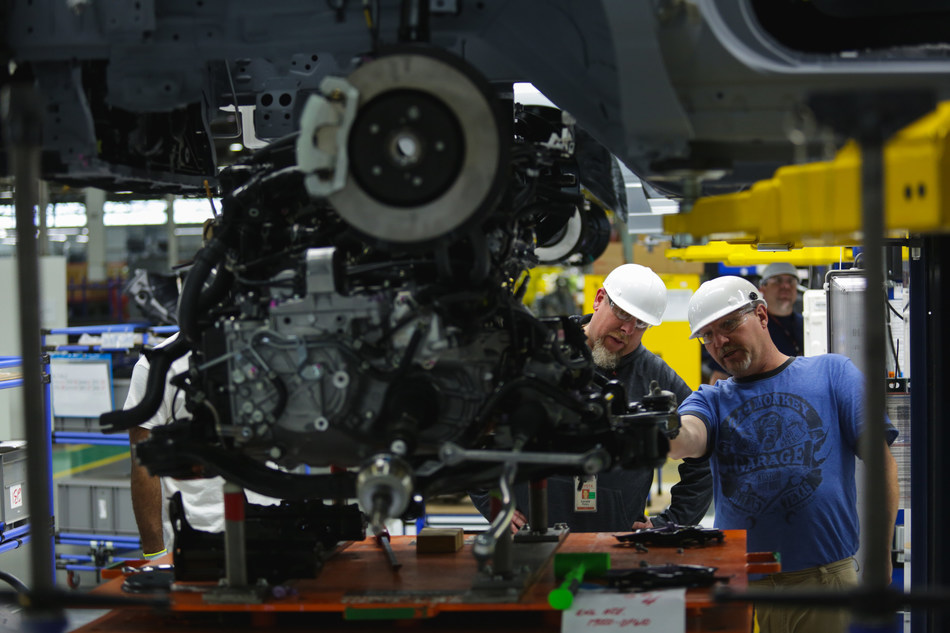 Toyota R&D employees study the underside of a vehicle at the newly opened TMNA R&D Purchasing and Prototype Development centers in York Township, Mich.