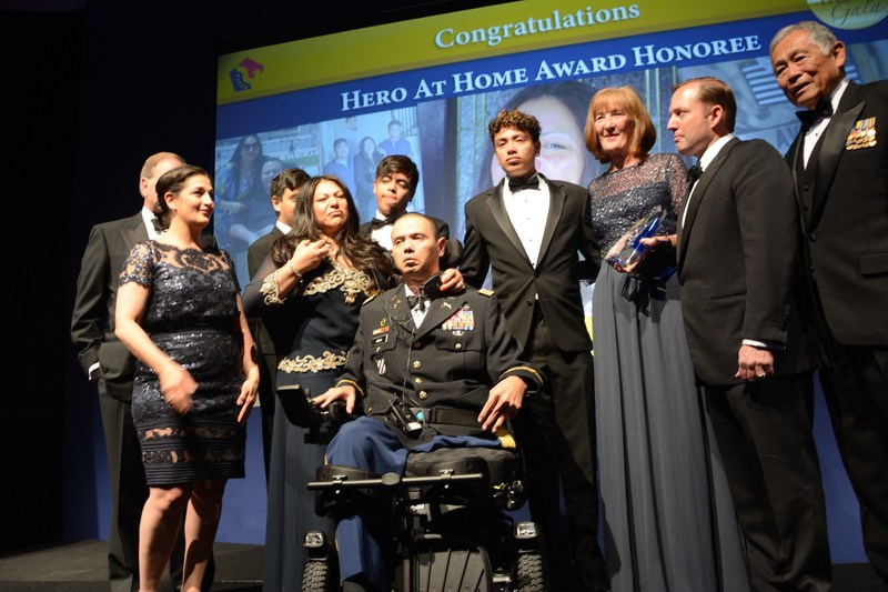 Claudia (second from left) and U.S. Army Captain Luis Avila on stage with their three sons, PenFed Foundation CEO James Schenck (second from right), The Honorable Frederick Pang, Chairman of the PenFed Foundation (far right), Tammy Darvish, PenFed Foundation President (far left) and Julie Keys, 2016 Hero at Home Award recipient.