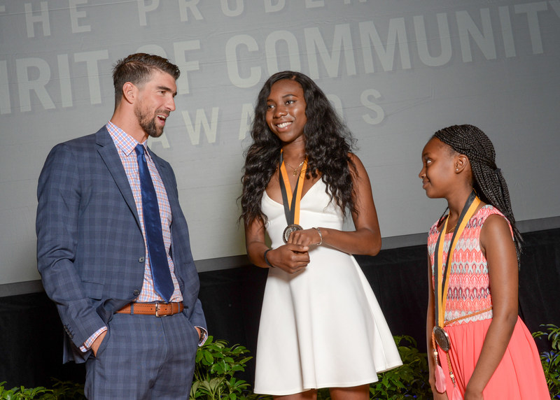 Olympic gold medalist Michael Phelps congratulates Ayomide Okuleye, 17 (center) and Debora Abera, 11 (right), on being named the District of Columbia's top two youth volunteers for 2017 by The Prudential Spirit of Community Awards. Ayomide and Debora were honored at a ceremony on Sunday, May 7 at the Smithsonian's National Museum of Natural History, where they each received a $1,000 award.