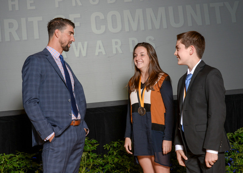 Olympic gold medalist Michael Phelps congratulates Annie Farrell, 18, of Miami (center) and Chase Hartman, 11, of Tampa (right) on being named Florida's top two youth volunteers for 2017 by The Prudential Spirit of Community Awards. Annie and Chase were honored at a ceremony on Sunday, May 7 at the Smithsonian's National Museum of Natural History, where they each received a $1,000 award.