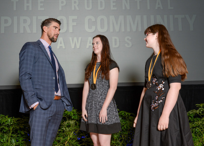 Olympic gold medalist Michael Phelps congratulates Grace McGowan, 18, of Overland Park (center) and Sydney Smith, 13, of Hiawatha (right) on being named Kansas' top two youth volunteers for 2017 by The Prudential Spirit of Community Awards. Grace and Sydney were honored at a ceremony on Sunday, May 7 at the Smithsonian's National Museum of Natural History, where they each received a $1,000 award.