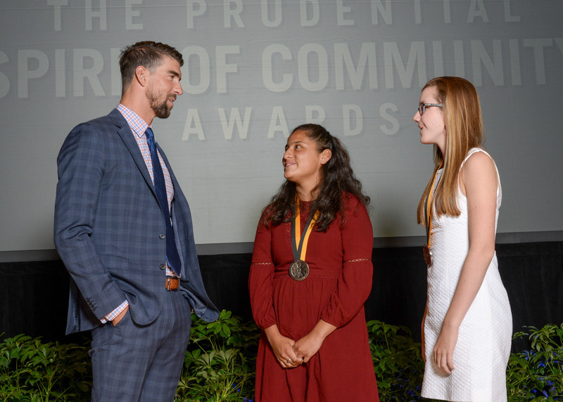 Olympic gold medalist Michael Phelps congratulates Gabrielle Metz, 17, of St. Albans (center) and Riley Callen, 14, of Pawlet (right) on being named Vermont's top two youth volunteers for 2017 by The Prudential Spirit of Community Awards. Gabrielle and Riley were honored at a ceremony on Sunday, May 7 at the Smithsonian's National Museum of Natural History, where they each received a $1,000 award.