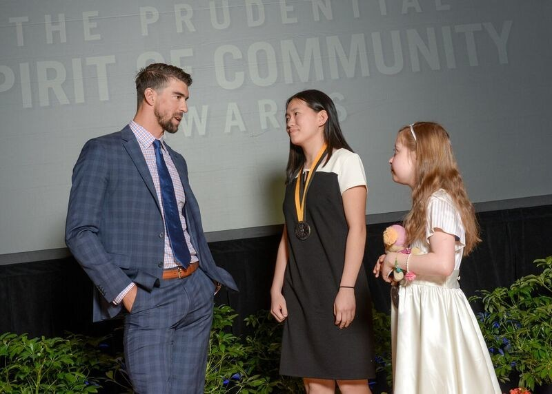 Olympic gold medalist Michael Phelps congratulates Amanda Yang, 16, of Dresher (center) and Lorelei McIntyre-Brewer, 11, of Duncannon (right) on being named Pennsylvania's top two youth volunteers for 2017 by The Prudential Spirit of Community Awards. Amanda and Lorelei were honored at a ceremony on Sunday, May 7 at the Smithsonian's National Museum of Natural History, where they each received a $1,000 award.